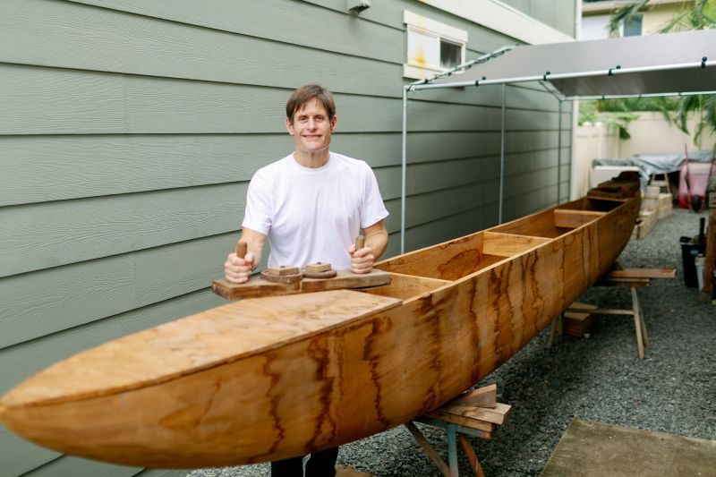 Rick Hobson finishing his handcrafted koa fishing canoe